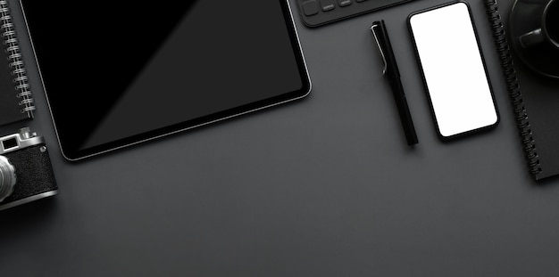 Top view of dark luxury workspace with copy space and office supplies on grey background