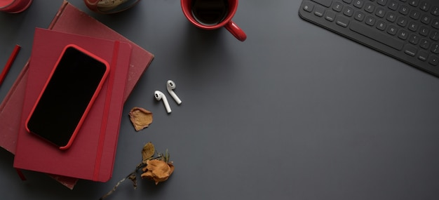Top view of dark luxury workspace with red notebooks and copy space with office supplies
