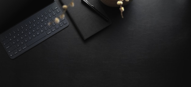 Top view of dark modern workspace with tablet and office supplies on black leather desk