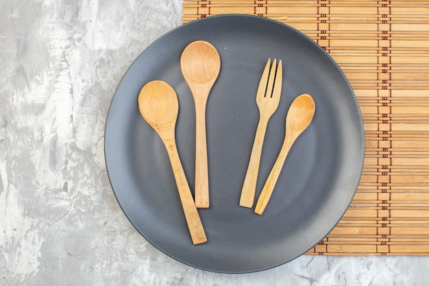 Top view dark plate with wooden spoons on light surface kitchen ladies horizontal food colour glass family femininity