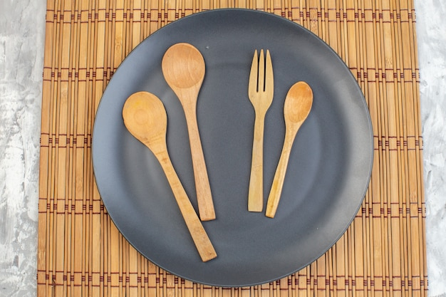 Top view dark plate with wooden spoons on light surface kitchen ladies horizontal food colour meal glass family femininity