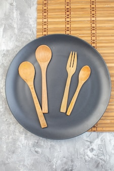 Top view dark plate with wooden spoons on light surface kitchen ladies horizontal food colour meal glass family
