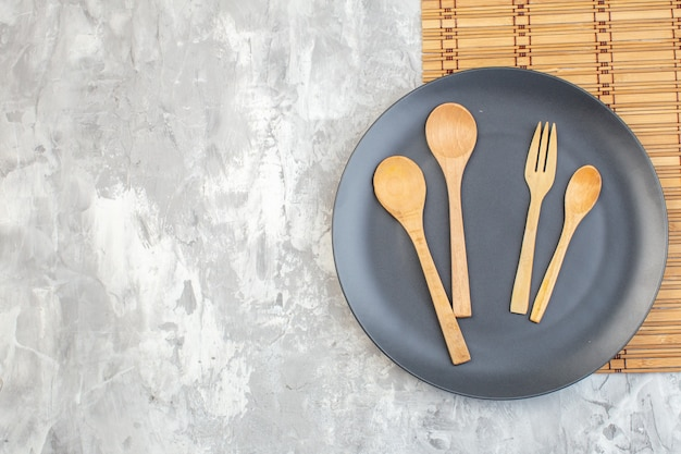 Top view dark plate with wooden spoons on light surface kitchen ladies horizontal food colour meal glass femininity