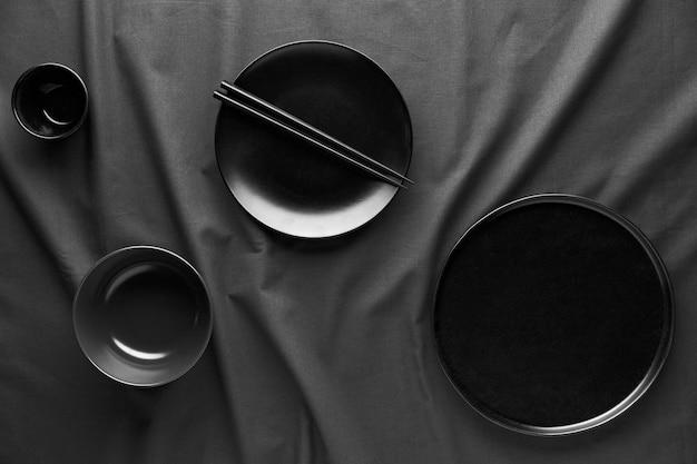 Vista dall'alto di piatti scuri e bacchette