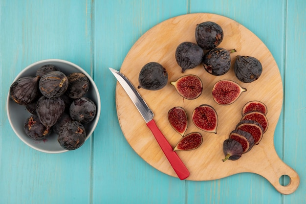 Top view of dark purple mission figs on a wooden kitchen board black figs on a bowl with knife on a blue wooden wall