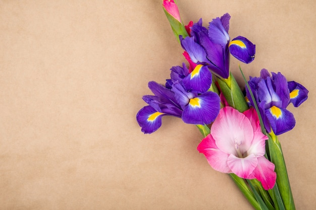 Top view of dark purple and pink color iris and gladiolus flowers isolated on brown paper texture background with copy space