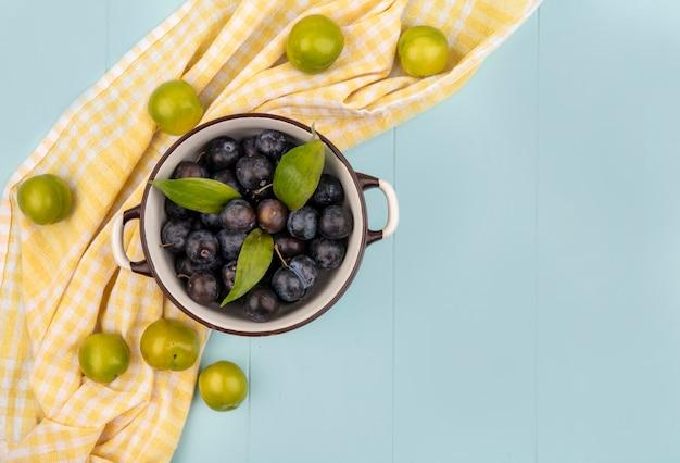 Vista dall'alto di prugnole viola scuro su una ciotola con prugne ciliegia verdi isolate su una tovaglia a quadretti gialla su sfondo blu con spazio di copia