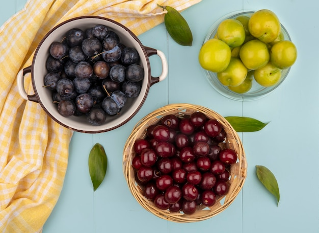 Top view of dark purple sloes on a bowl with red cherries on a bucket with green cherry plums on a blue background
