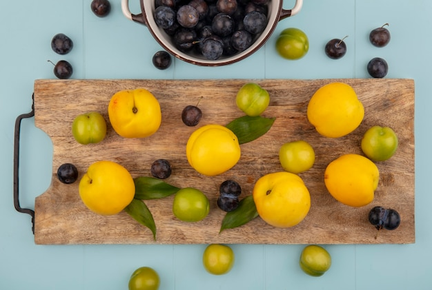Top view of dark purple sloes on a bowl with yellow peaches isolated on a wooden kitchen board on a blue background