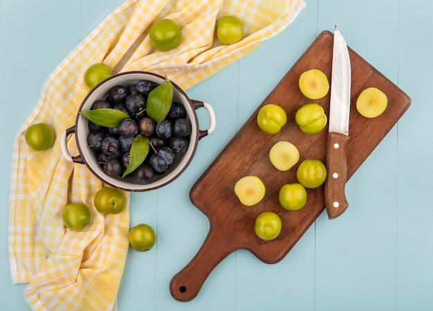 Vista dall'alto di prugnole acide viola scuro su una ciotola con fette di prugne ciliegie verdi su una tavola da cucina in legno con coltello su sfondo blu