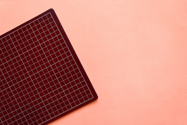 Top view of dark red rubber cutting mat on the left side over pink color paper background. background with copy space.