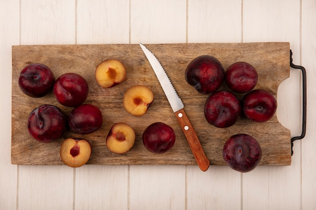 Top view of dark red and sweet pluots on a wooden kitchen board with knife on a beige wooden background