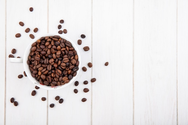 Top view of dark roasted coffee beans on a white cup on a white wooden background with copy space