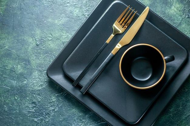 어두운 배경 칼 붙이 레스토랑 점심 색상 플레이트 차 음료에 황금 포크 나이프와 컵 상위 뷰 어두운 사각형 접시