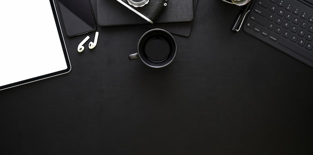 Top view of dark stylish workplace with office supplies