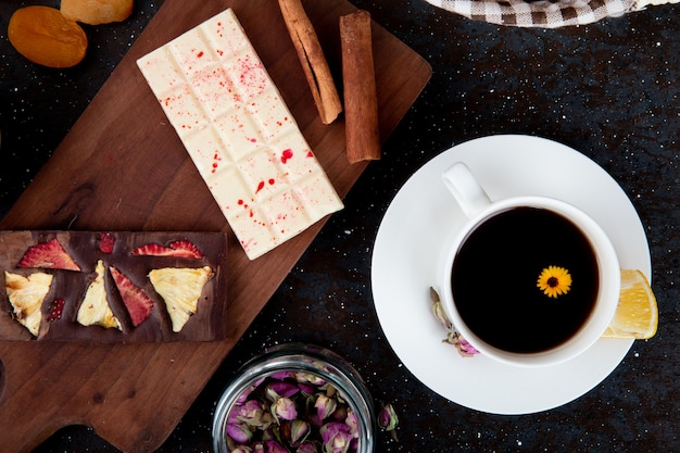 Top view of dark and white chocolate bars with cinnamon sticks on a wooden board and a cup of tea on rustic