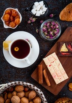 Top view of dark and white chocolate bars with cinnamon sticks on a wooden board and dried fruits, walnuts and a cup of tea on rustic