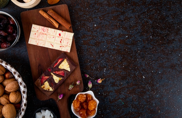 Vista superiore delle barre di cioccolata fondente e bianca con i bastoni di cannella sul bordo di legno e con la frutta secca e le noci sul nero con lo spazio della copia