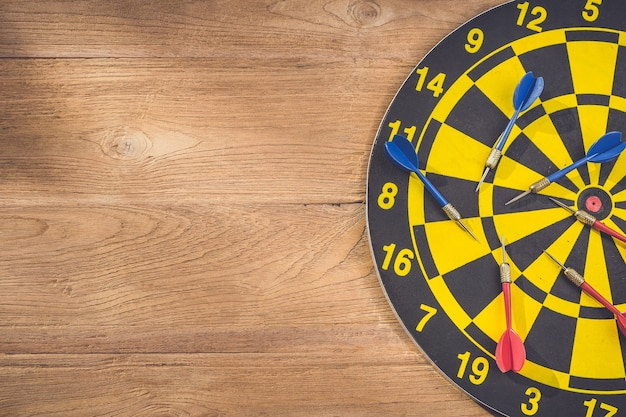 Top view dart arrow and dartboard on brown wooden background