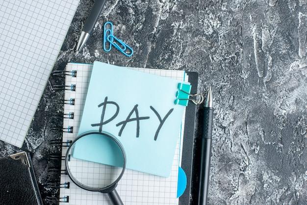 灰色の背景にコピーブックとペンでトップビューの日のメモ