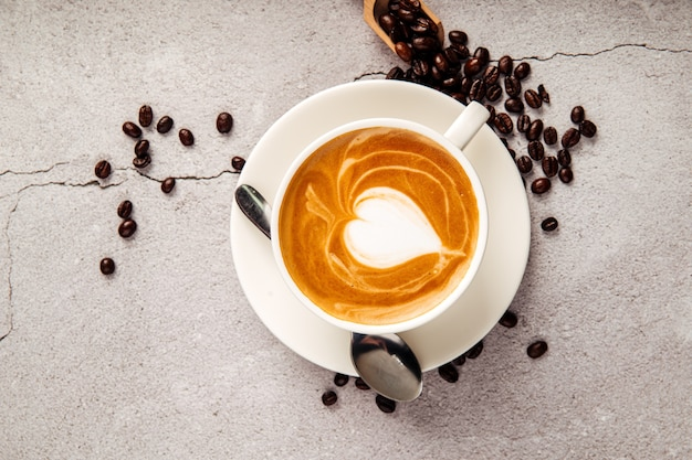 Top view on decorated cappuccino coffee in a  white cup on the concrete background
