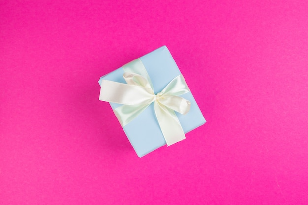 Top view of a decorated present with a bow on pink background