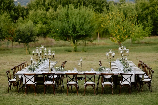 Top view of decorated with minimal floral bouquets and candles wedding celebration table with chiavari seats outdoors in the gardens in front of fruits trees