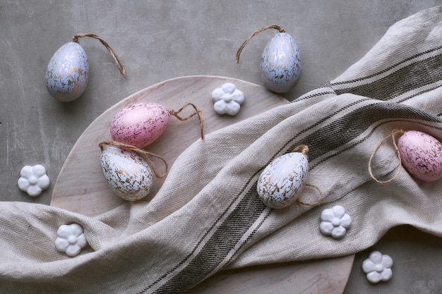 Top view of decorative handmade easter eggs in pastel colors on wooden tray