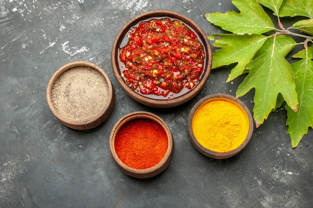 Top view delicious adjika hot pepper powder turmeric in small bowls leaves on grey background