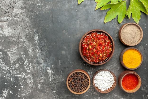회색 배경에 있는 작은 그릇에 다른 향신료를 넣은 나무 그릇에 있는 맛있는 아지카