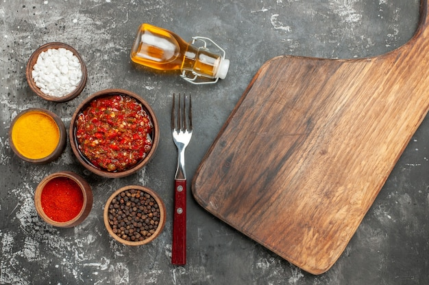 Top view delicious adjika wooden serving board with handle different spices in small bawls oil fork on grey background