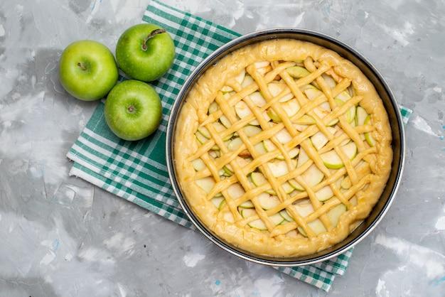 Una deliziosa torta di mele con vista dall'alto si forma all'interno della padella con mele verdi fresche sul biscotto leggero della torta della scrivania