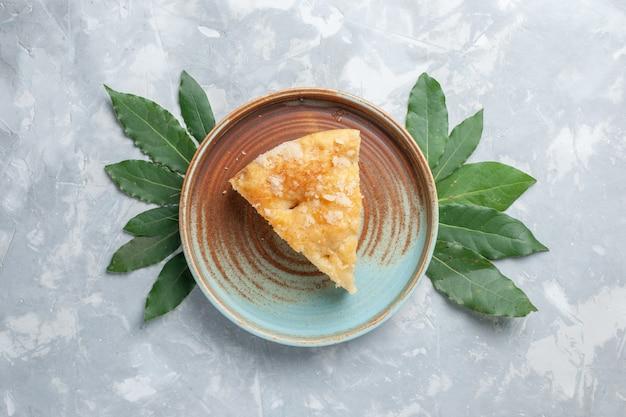 Вид сверху вкусный яблочный пирог внутри тарелки на белом столе пирог, бисквит, сладкая выпечка с сахаром