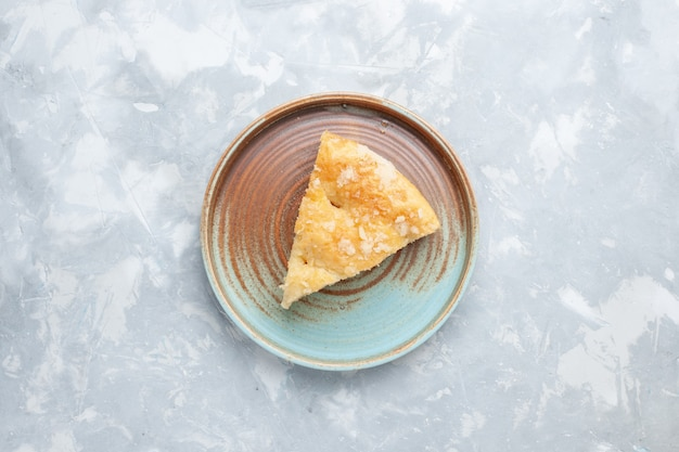 Вид сверху вкусного яблочного пирога, нарезанного внутри тарелки на белом столе, пирог, сладкое печенье, выпечка