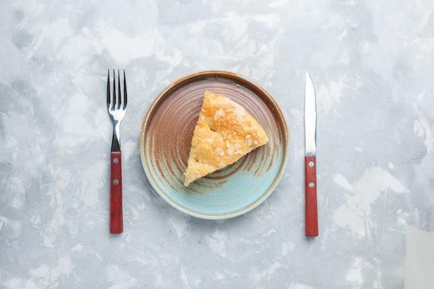 Vista dall'alto deliziosa torta di mele affettata all'interno della piastra sulla scrivania bianca torta torta di zucchero dolce cuocere il biscotto