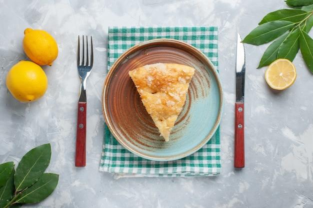 上面図白い机の上のレモンとプレートの内側にスライスされたおいしいアップルパイパイケーキ甘い砂糖焼きビスケット