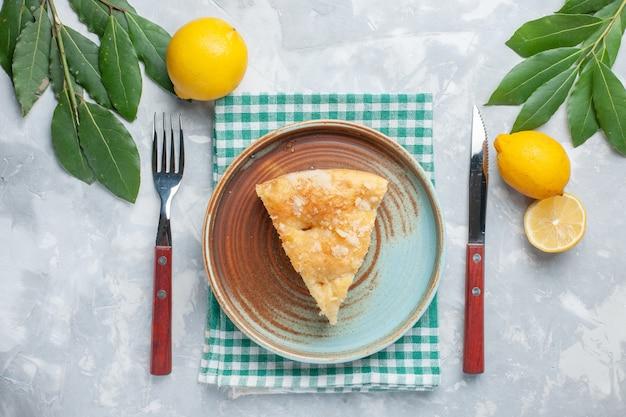 Вид сверху вкусный яблочный пирог, нарезанный внутри тарелки с лимонами на белом столе, пирог, пирог, выпечка бисквита