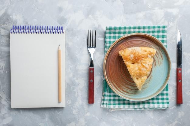 Вид сверху вкусный яблочный пирог, нарезанный внутри тарелки с блокнотом на белом столе, пирог, пирог, сладкий сахар, выпечка, печенье