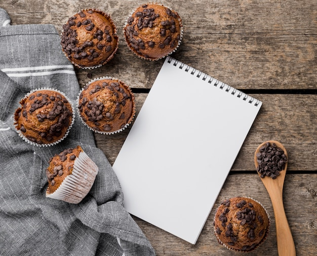 Top view delicious arrangement of muffin and notepad