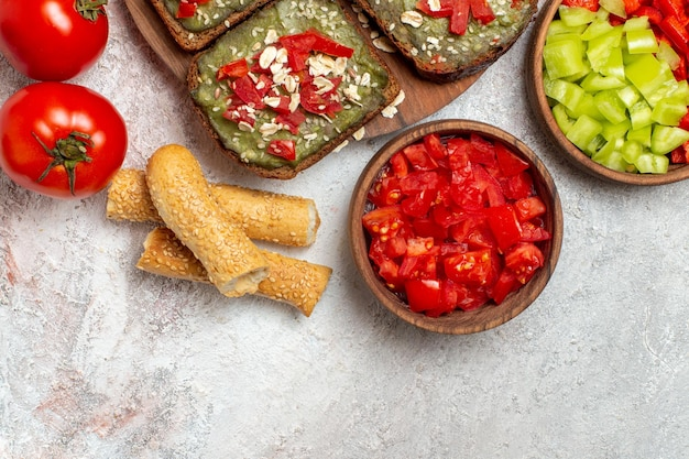 Top view of delicious avocado sandwiches with fresh red tomatoes on white surface