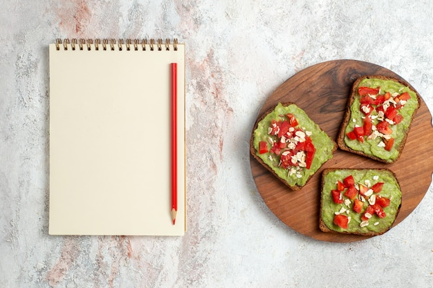 Top view of delicious avocado sandwiches with sliced red tomatoes on white surface