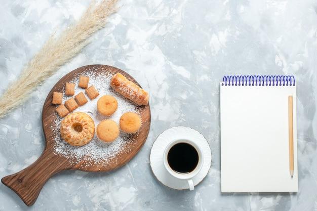 Вид сверху вкусный рогалик с чашкой чая и пирожными на светлом белом фоне.