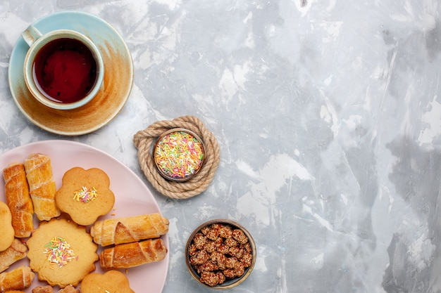 白い机の上にケーキとお茶とトップビューのおいしいベーグル