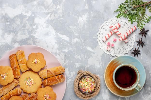 Вид сверху вкусные рогалики с пирожными и чаем на белом столе
