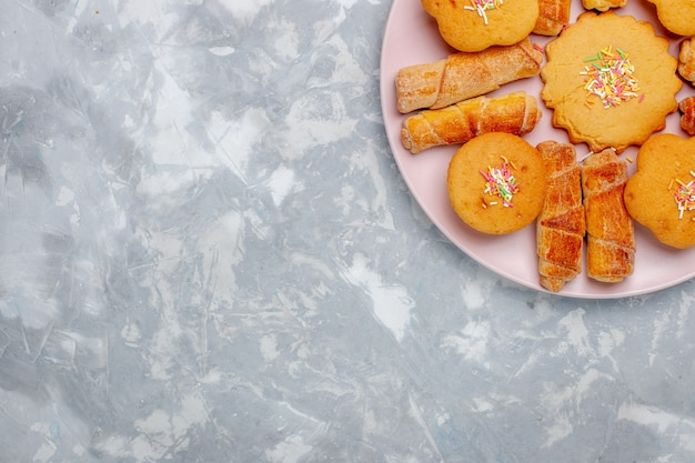 Vista dall'alto deliziosi bagel con torte all'interno del piatto sulla scrivania bianca chiara