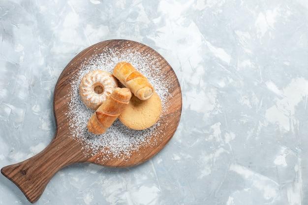 Vista dall'alto deliziosi bagel con torte su sfondo bianco chiaro.