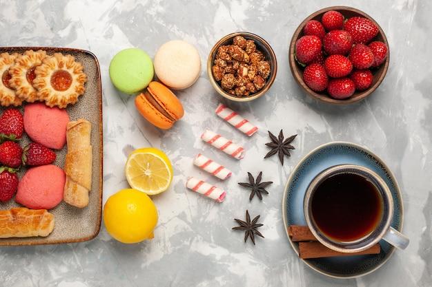 白い机の上にケーキ、お茶、新鮮なイチゴとクッキーとトップビューのおいしいベーグル