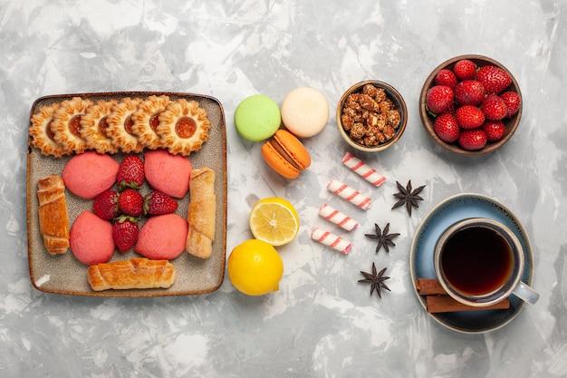 白い机の上にケーキティー新鮮なイチゴ茶とクッキーとトップビューのおいしいベーグル