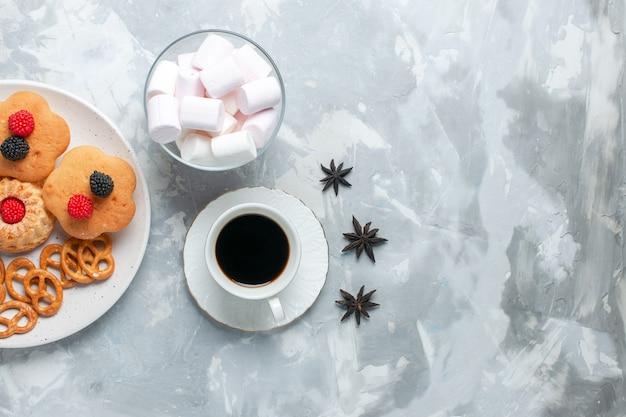 Вид сверху вкусные рогалики с печеньем, крекерами и пирожными с чаем на светло-белом столе.
