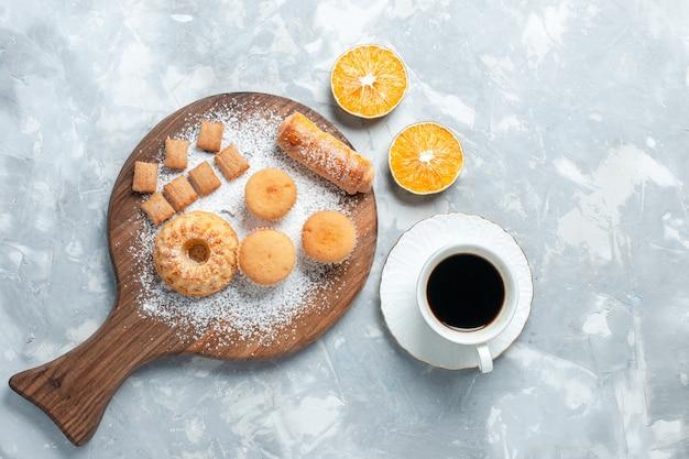 Вид сверху вкусные рогалики с чашкой чая и пирожными на светло-белом фоне.